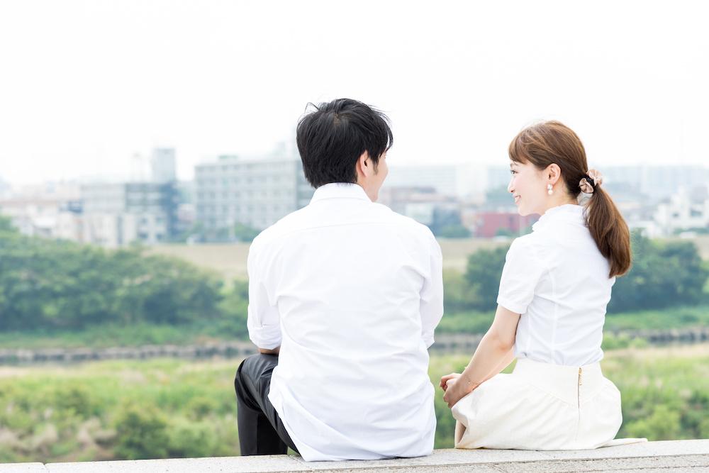 屋外で座って会話するカップル