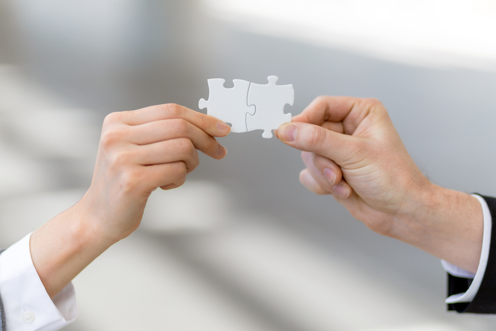 man and woman hand holding jigsaw puzzles, business matching concept